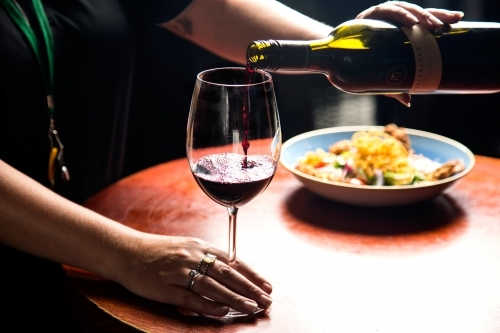 Woman pouring a glass of wine with meal in background