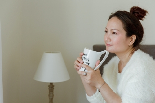 Woman relaxing and drinking tea at home