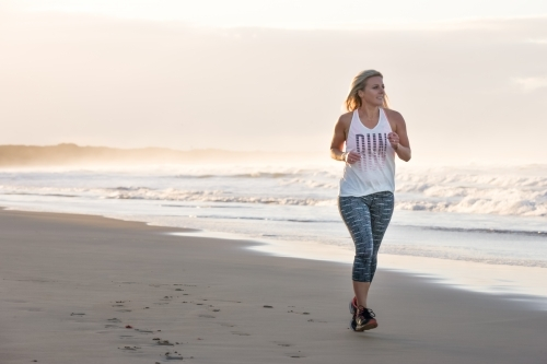 woman running on a beach in the early morning