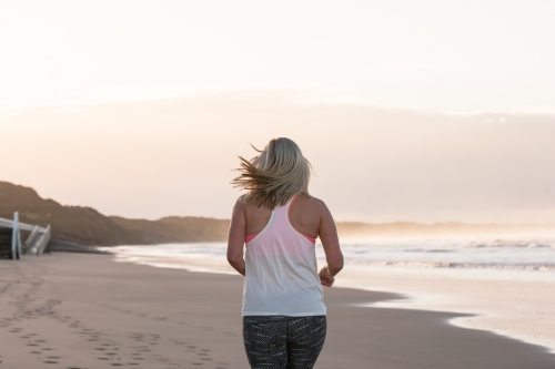 woman running on the beach in the early morning