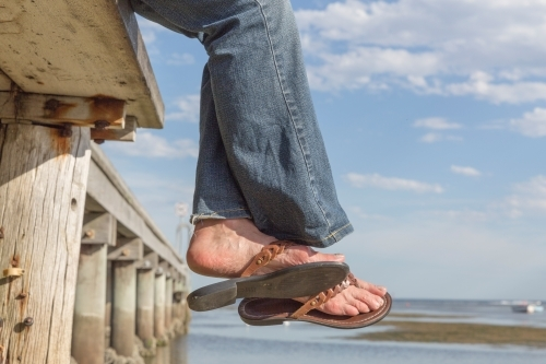 Woman's feet in sandals off the edge of a timber pier