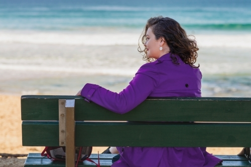 woman sitting on a bench by the sea
