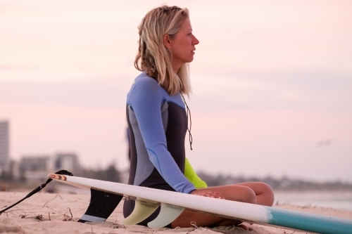 Woman sitting on beach next to surfboard wearing wetsuit looking out to sea at sunrise