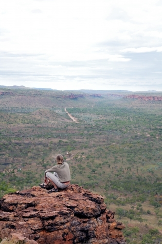 Woman sitting on clifftop in outback Australia