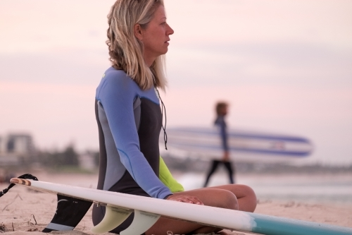 Woman sitting on shoreline with hand on surfboard looking out to sea