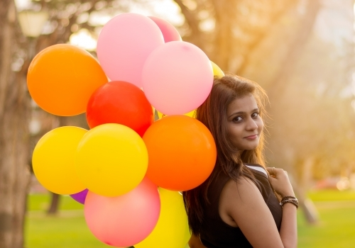 Woman smiling and holding balloons