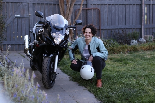 Woman smiling next to motorbike in garden