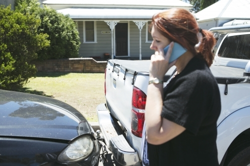 Woman standing beside car accident