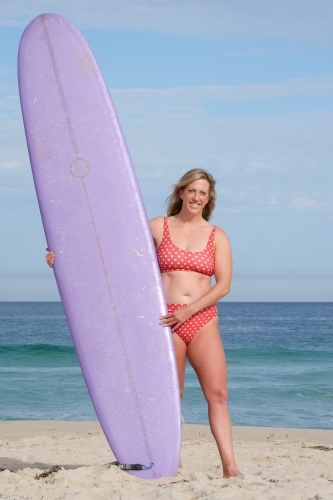 Woman standing on beach holding longboard surfboard looking at camera