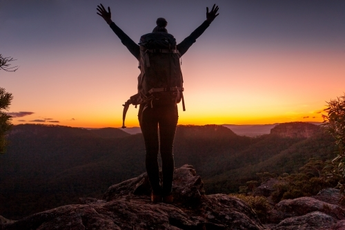 Woman standing on top of mountain peak views to escarpment and valleys, hands in air with feelings o
