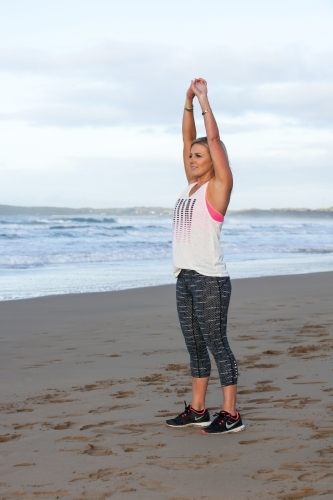 Woman stretching and exercising at the beach