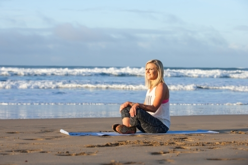 woman stretching on a mat at the beach