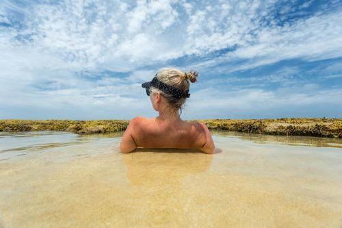 Woman sunbathing in shallow water