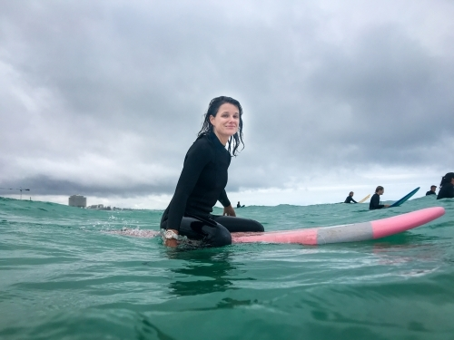 Woman surfer sitting on soft surfboard in ocean looking at camera