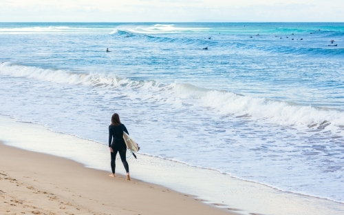 Woman Surfer walking on the beach with Surfboard with surfers in the sea