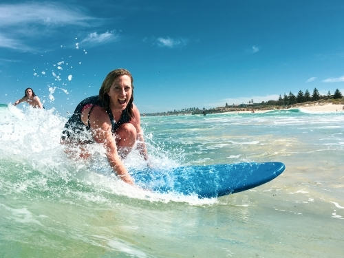 Woman surfing wave on soft board surfboard laughing