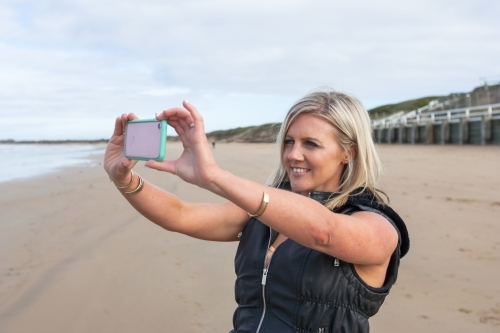 woman taking a photo at the beach
