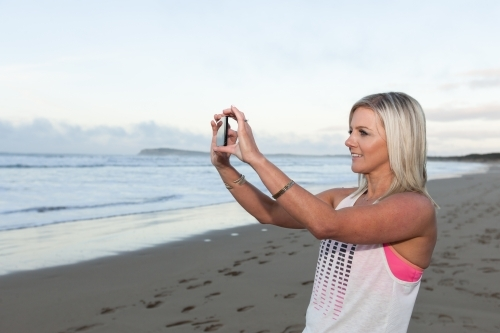 woman taking a photo at the beach on her phone