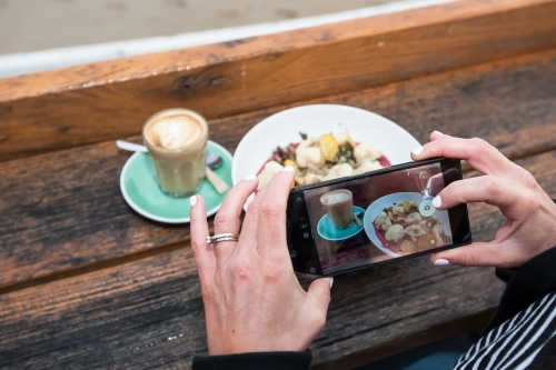 woman taking a photo of her breakfast at a cafe