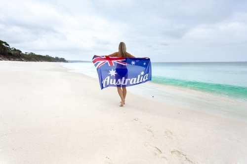 Woman walking along the beach holding Australian Flag