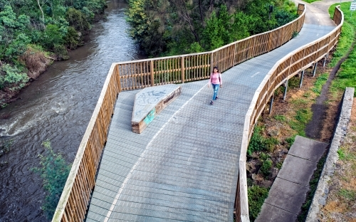 Woman walking on a bridge along the Merri Creek Trail