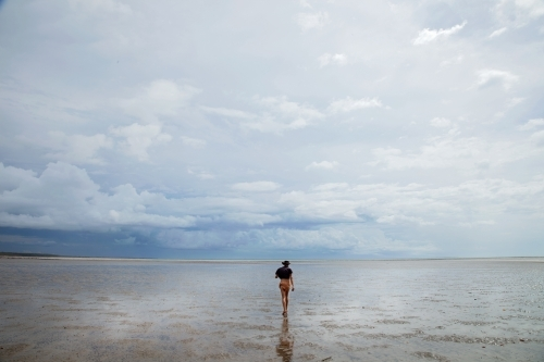 Woman walking out across shallow water