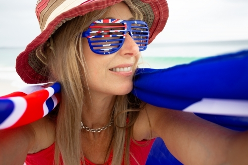 Woman wearing Australia flag sunglasses and with flag draped around her shoulders