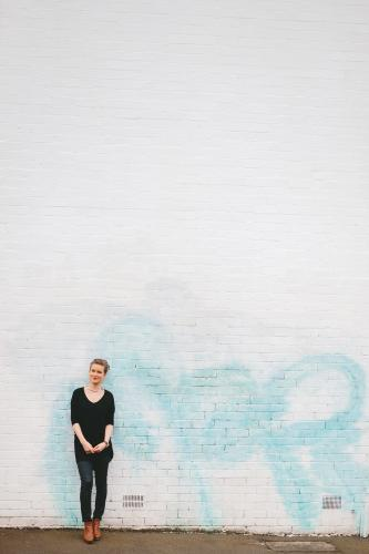 Woman wearing black against white brick wall