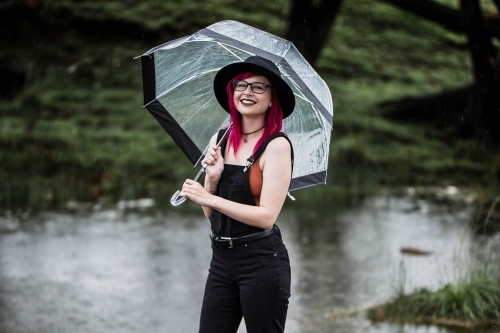 Woman with pink hair standing in rain holding umbrella near river
