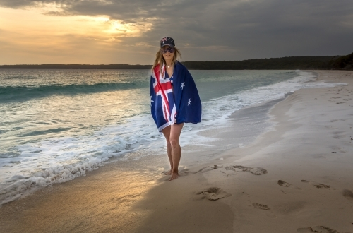 Woman with the Australian flag wrapped around, wears a hat and sunglasses