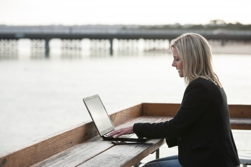 woman working on her laptop at a coastal location