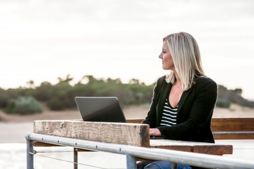 Woman working on her laptop in coastal location