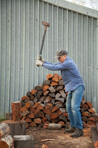 Man splitting logs of wood for fire in winter