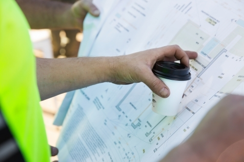 Workers' hands on building plans at a construction site