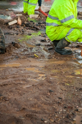 Workers in hi-vis gear around a mud hole in the road