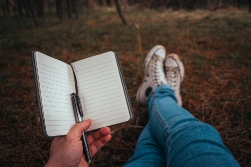 Writing in an Empty Journal while sitting in a forest.