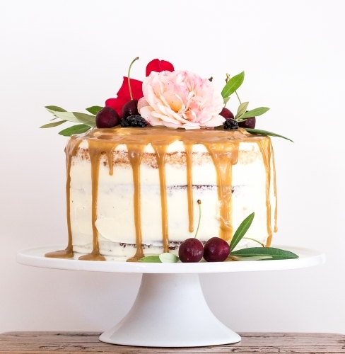 A birthday cake with flowers and fruit on a cake stand