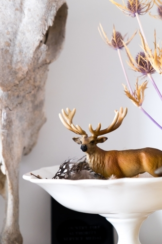Toy deer in a bowl with feathers and dried seed heads