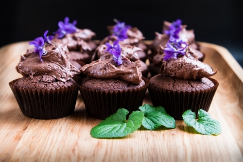 Chocolate cup cakes with frosting and flowers