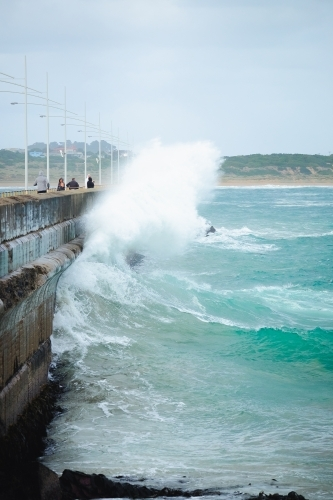 People walk along the breakwater as a huge wave crashes