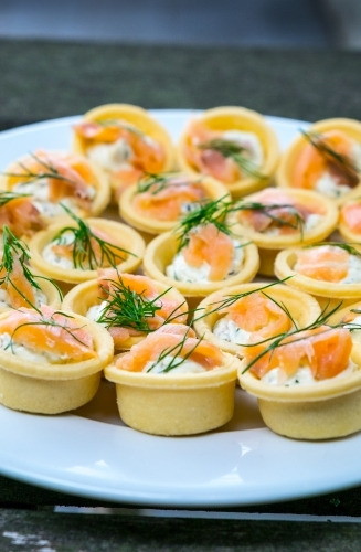 Small smoked salmon and dill tarts on a plate