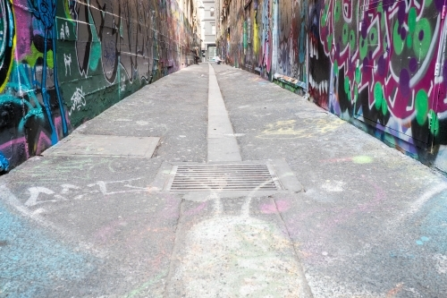 Melbourne laneway with street artist at work in the distance