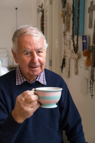 Old man with a cup of tea looks at the camera