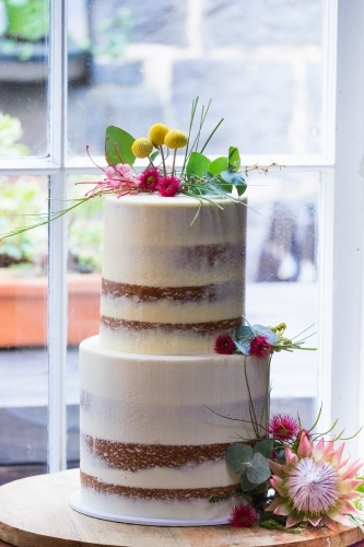 Wedding cake with native flowers in a window