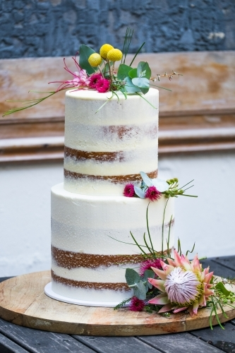 Celebration white layer cake with flowers on table