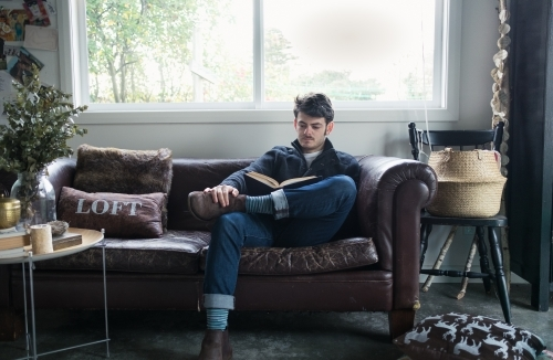 Young man reading a book on a worn leather sofa