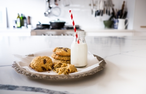 Fresh baked chocolate chip cookies and milk on the kitchen bench.