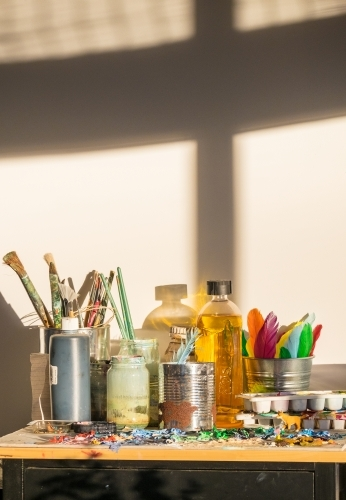 Shadows and light in an art studio with painters brushes and paint palette