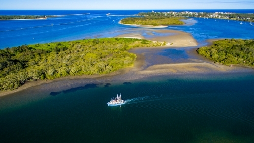 Aerial view of a trawler departing Yamba on the Clarence River