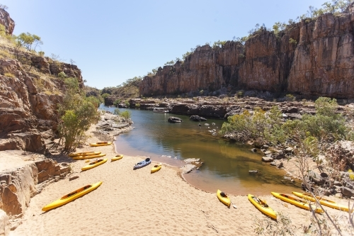 Yellow kayaks on beach in remote gorge